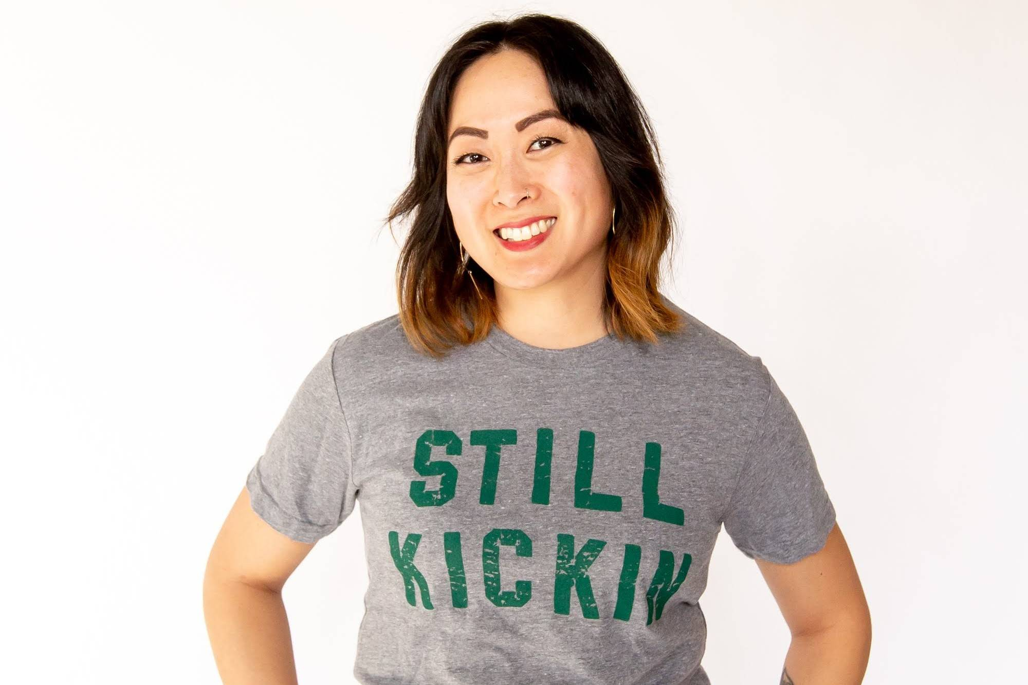 photo of Rebecca Sharbono wearing a grey t-shirt with green Still Kickin print