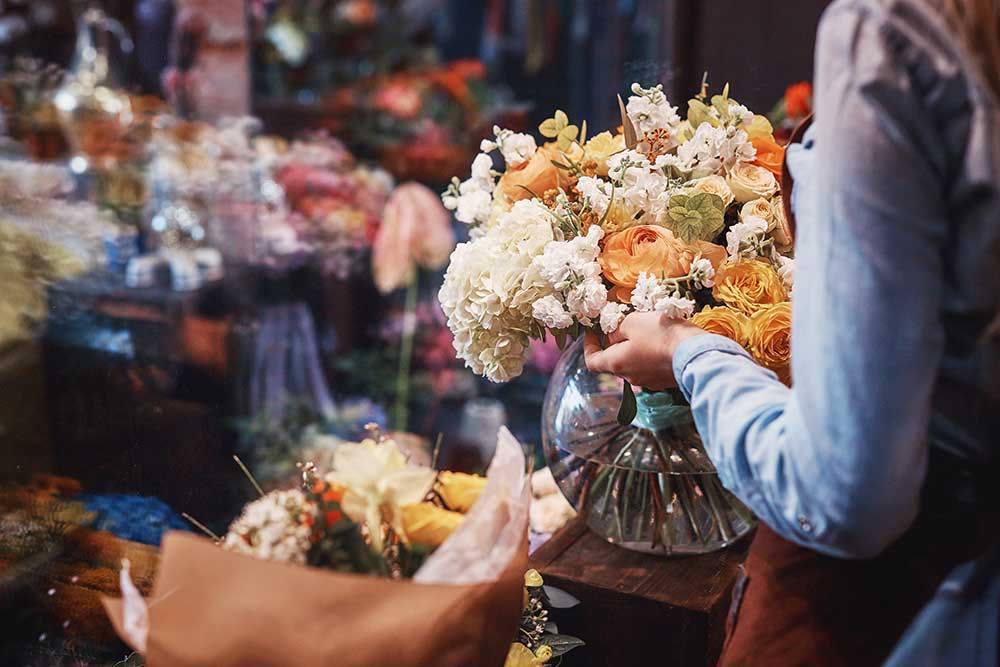 Picture of a florist designing a white and orange arrangement in a bowl