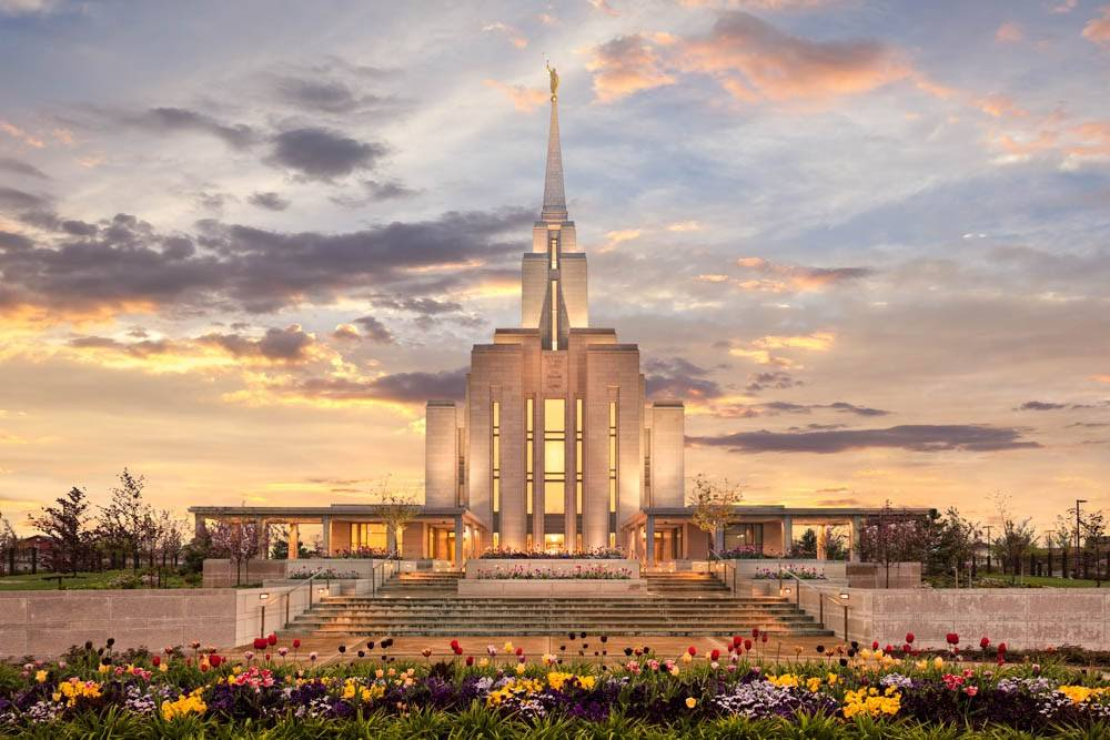 LDS art photo of the Oquirrh Mountain Temple among yellow flowers and a golden sky.