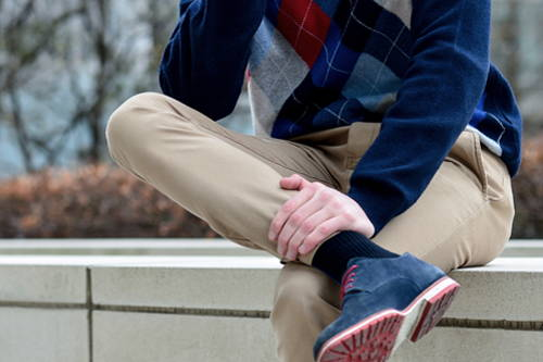 A young man sitting on a ledge grasping his leg while wearing compression socks