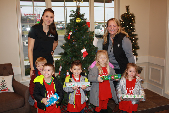 Children and teachers holding presents
