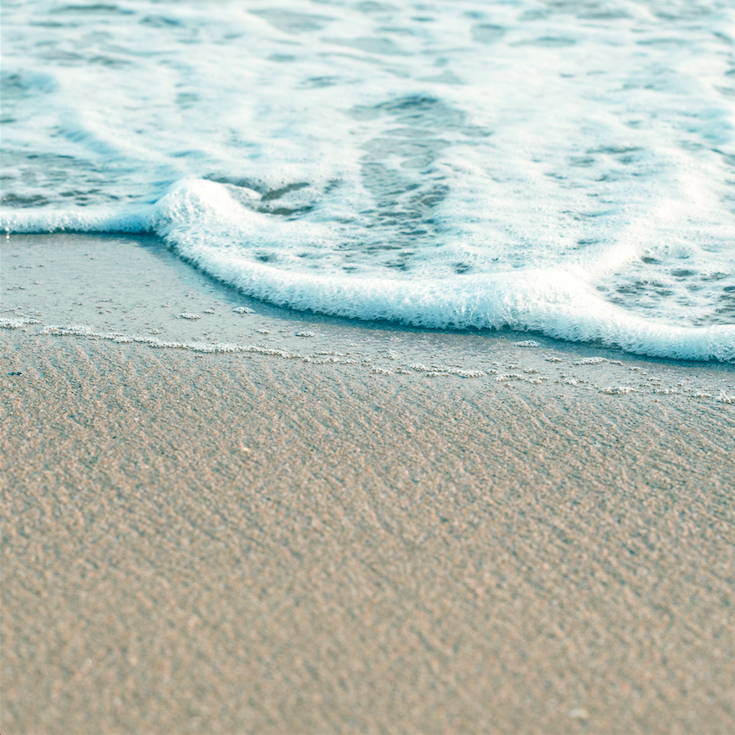 calm foamy ocean waves on a sandy beach