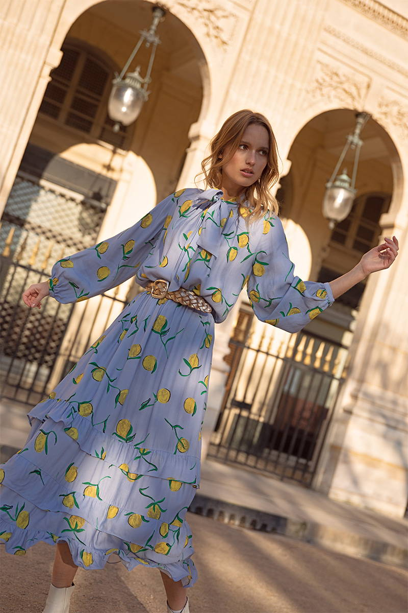 Philou Celaries wears the Lemon Jessica Blouse and Jezzabel Skirt print with bright yellow lemons  on a pale blue background