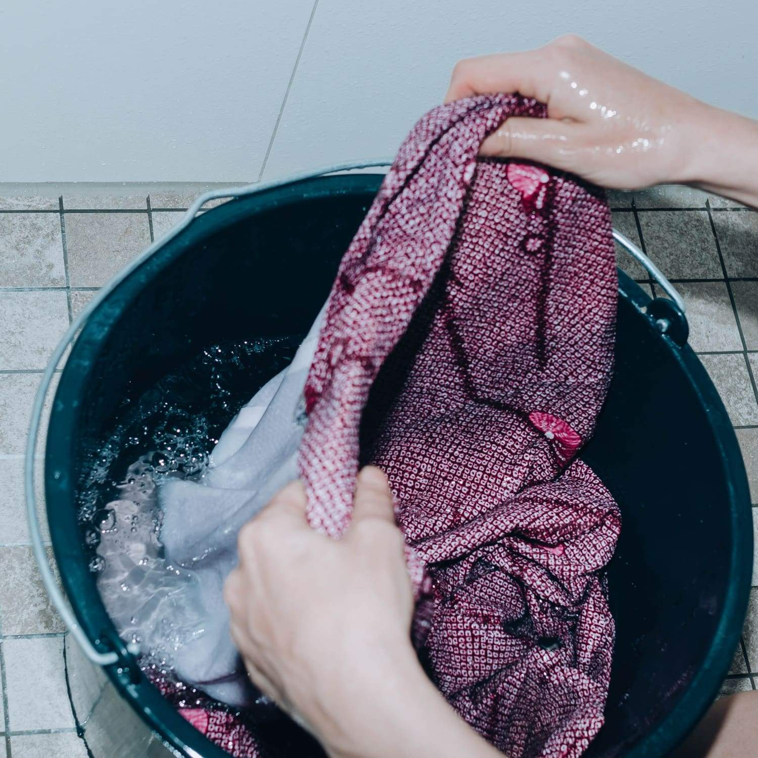 hands carefully lifting a washed kimono out of water