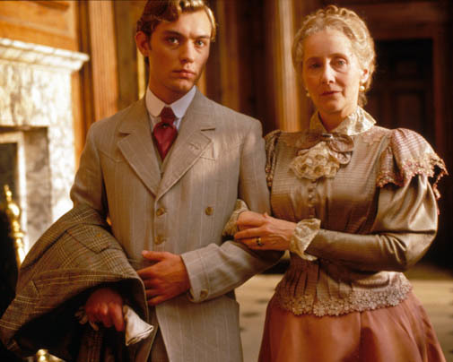 Movie still of Lord Alfred arm in arm with an older woman both looking into the camera worried.