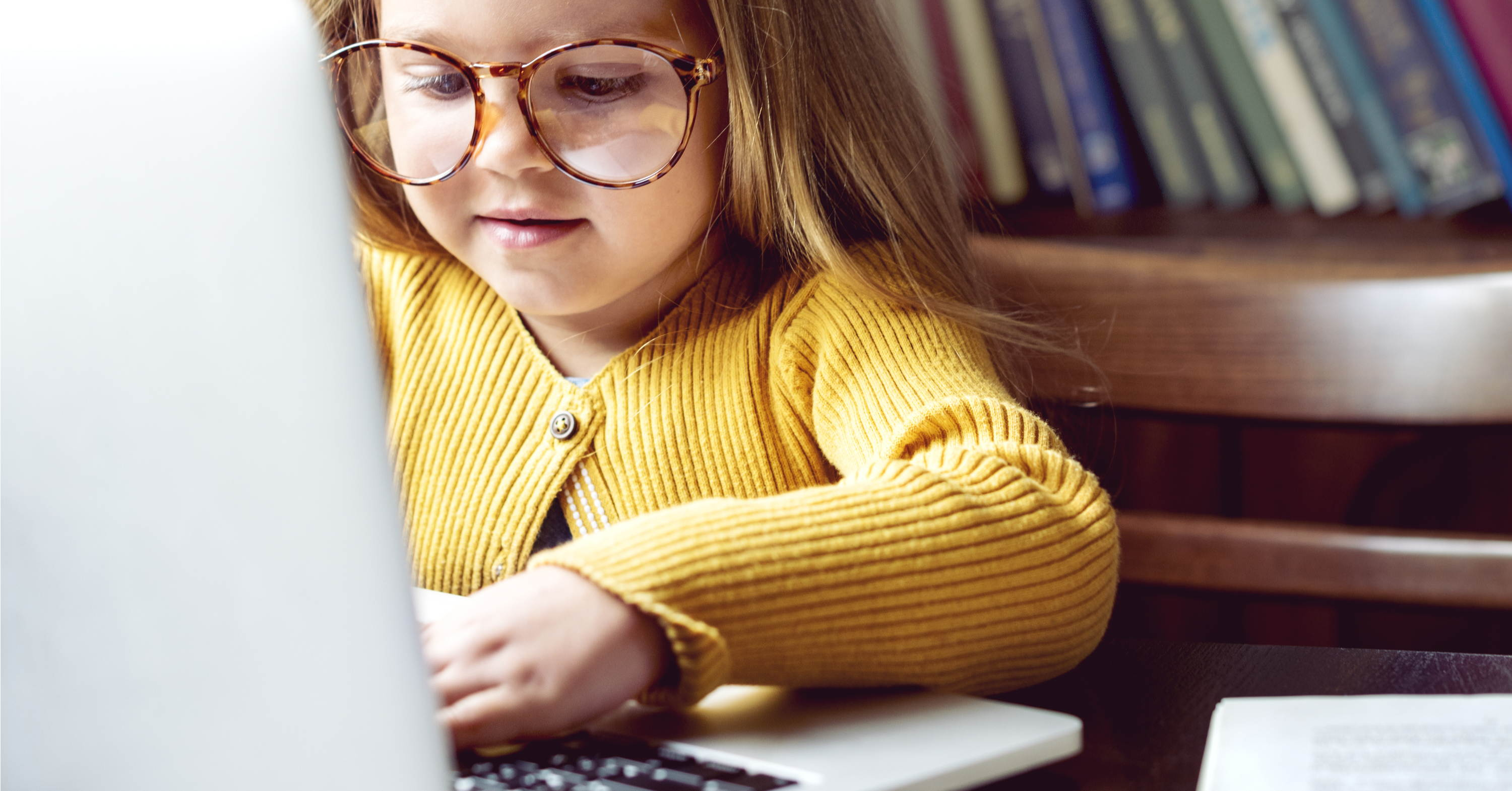 little girl with large glasses using laptop