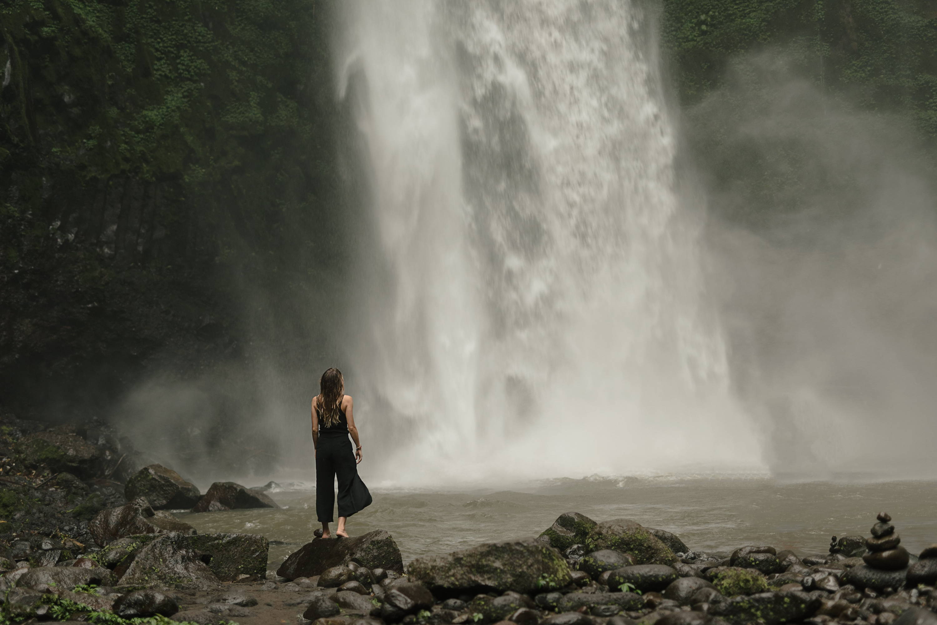 Small aperture: woman pauses at foot of waterfall