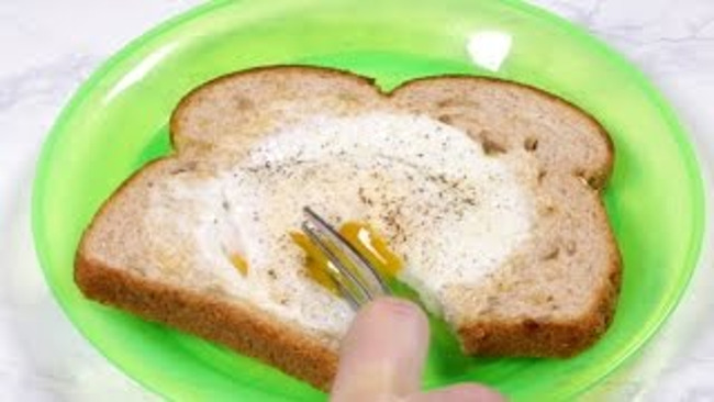 Close up of a child breaking into his one eyed jack breakfast using a fork