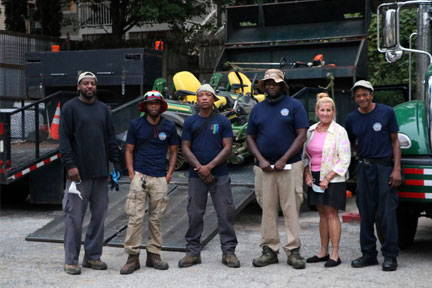 """A crew of six permanent employees and six seasonal employees are responsible for cleaning and maintaining ALL BeltLine trails and parks. (L-R: Darryl McDowell, Lee Levy, Aaron Smith, Jermari Anthony, Tucker Hutmacher, and Jeffrey Howard.) """"Previously I managed both greenhouse work and the BeltLine for Parks, but the BeltLine grew and grew, and that's been my sole responsibility for the last two years.""""   Hutmacher transforms a crude graffiti tag into something more family-friendly until her crew can properly pressure wash the corridor. On a given day, the crew does a garbage run for the 182 bins, cleans and restocks the restrooms, blows walkways, mows lawns, cleans up litter, and, depending on the people available, removes graffiti. Partnerships have been the key to getting things done, and given the scope and assortment of work involved, Hutmacher probably has one of the most coveted contact lists in town.  """"I love my job. Every day is different,"""" says the former teacher of horticulture who made her way to the City following the 2009 recession that terminated non-core programs in schools.  """"We usually have several volunteer programs to help with partners like Park Pride, Adopter Groups, Atlanta BeltLine Partnership or Georgia Tech, to name a few, but those have closed with COVID.""""  The cancellation of volunteer programs, coupled with increased trash piling up from restaurant to-go orders, have left the Parks BeltLine crew even more overloaded. To alleviate the trash problem, additional bins were placed in high-traffic areas, and ABI pushed out an additional etiquette campaign reminding folks to properly dispose of waste.  Recently, the Parks BeltLine team was the subject of a letter writing campaign, thanking them for their work.  """"Those people took the time to look up our address, write a letter, and put it in the mail. That made everyone feel good, but I would still like everyone to pick up their trash.""""   Thank you letters from grateful citizens adorn the exit d"""