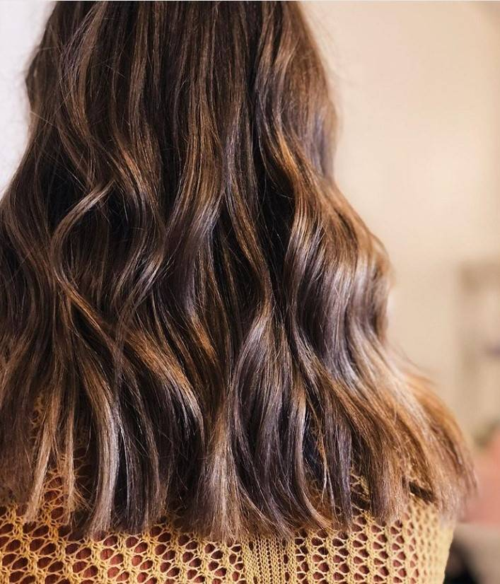 Back view of a woman with long wavy auburn brown hair
