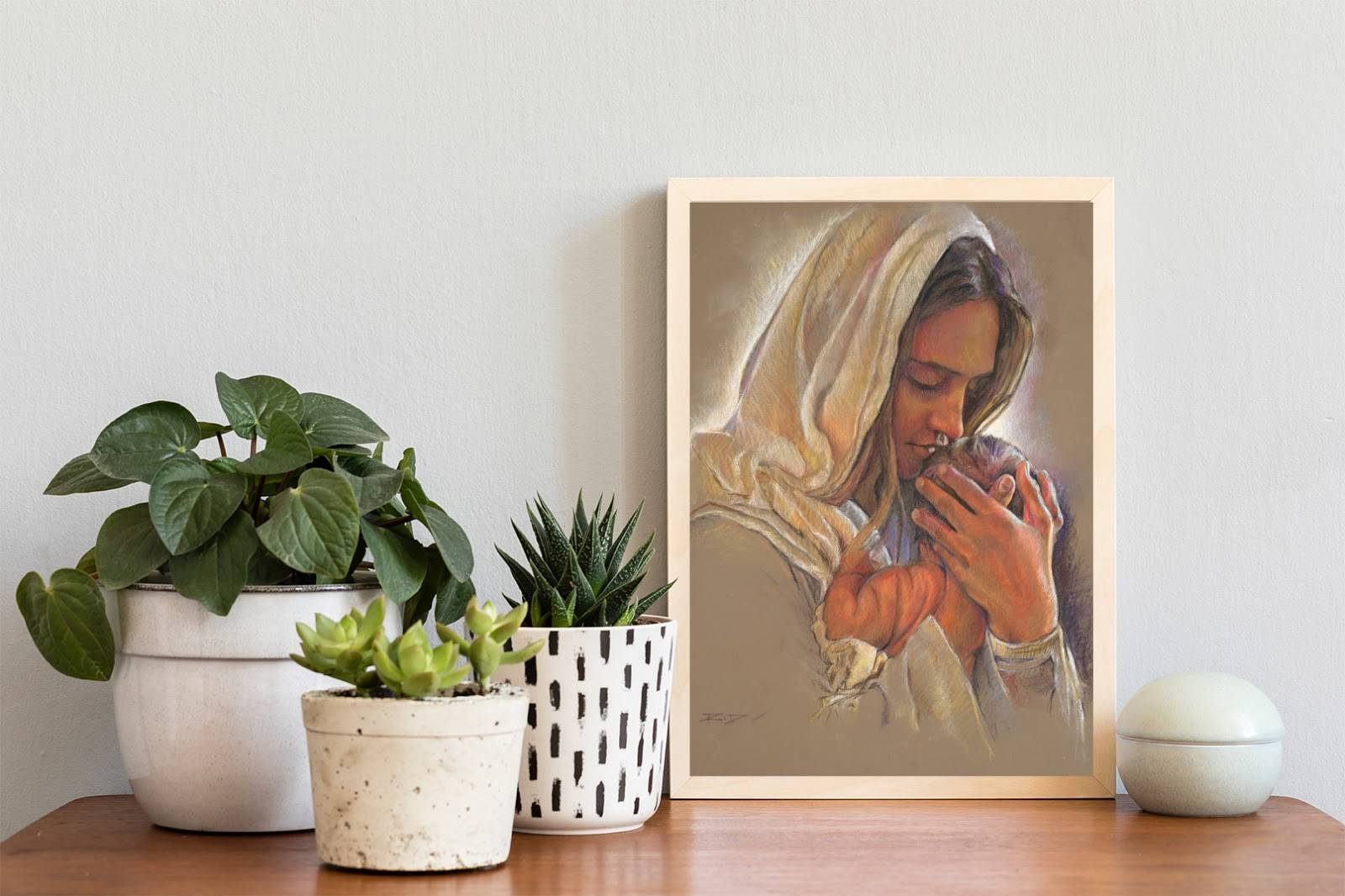 Small art painting of a mother holding her infant.  The picture has been placed on a small end table among various plants and decorative items.