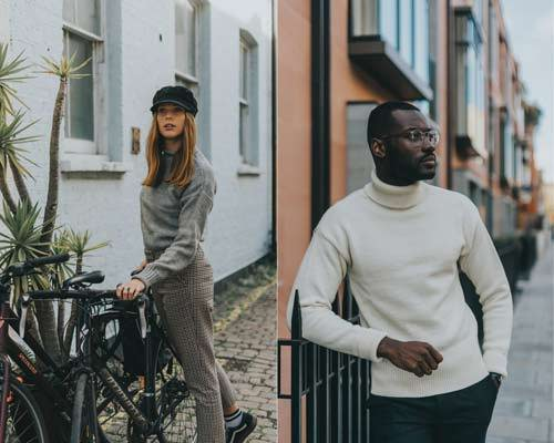 Woman wearing Grey fisherman jumper and man wearing cream submariner jumper with black trousers from sustainable knitwear brand Beacon and Armour