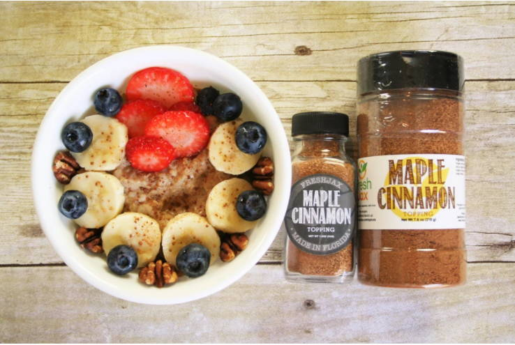 A bowl of Maple Cinnamon Oatmeal next to two bottles of FreshJax Organic Maple Cinnamon Topping.
