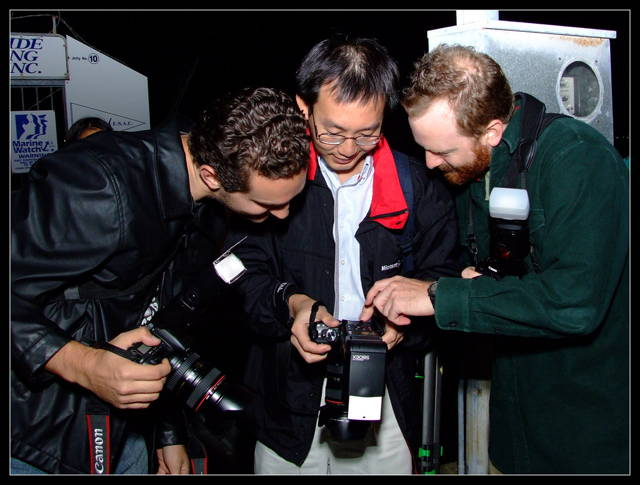 Three men were checking a photograph they had just taken
