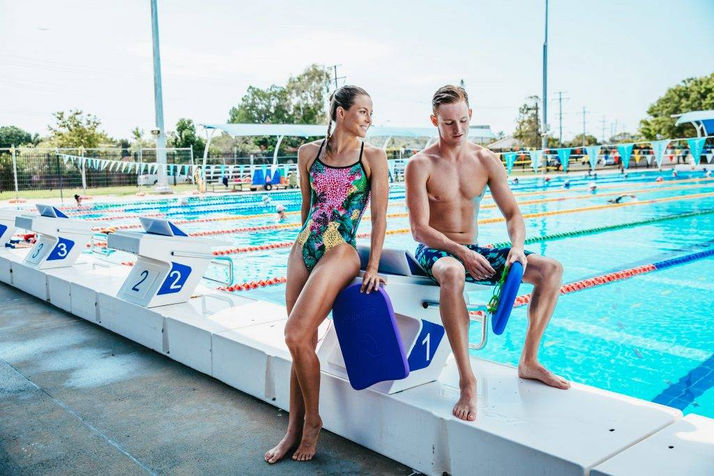 swimmers with kickboards, pull buoys waiting at the pool