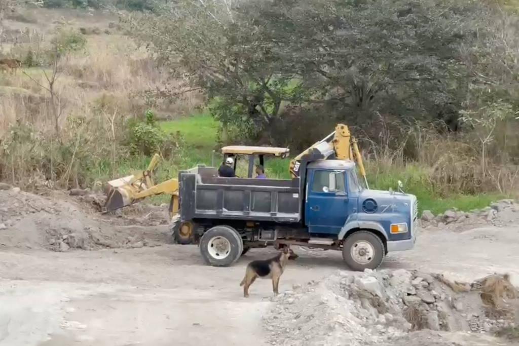 Dump truck and bulldozer building a water reservoir.