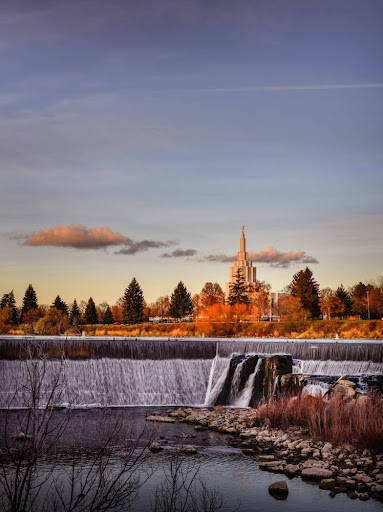 Idaho Falls temple surrounded by orange trees. Waterfalls in the foreground.