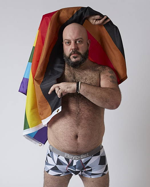 DJ Chauncey D wears Play Out gender-equal trunks underwear, looks at the camera, and holds a rainbow flag above his head.
