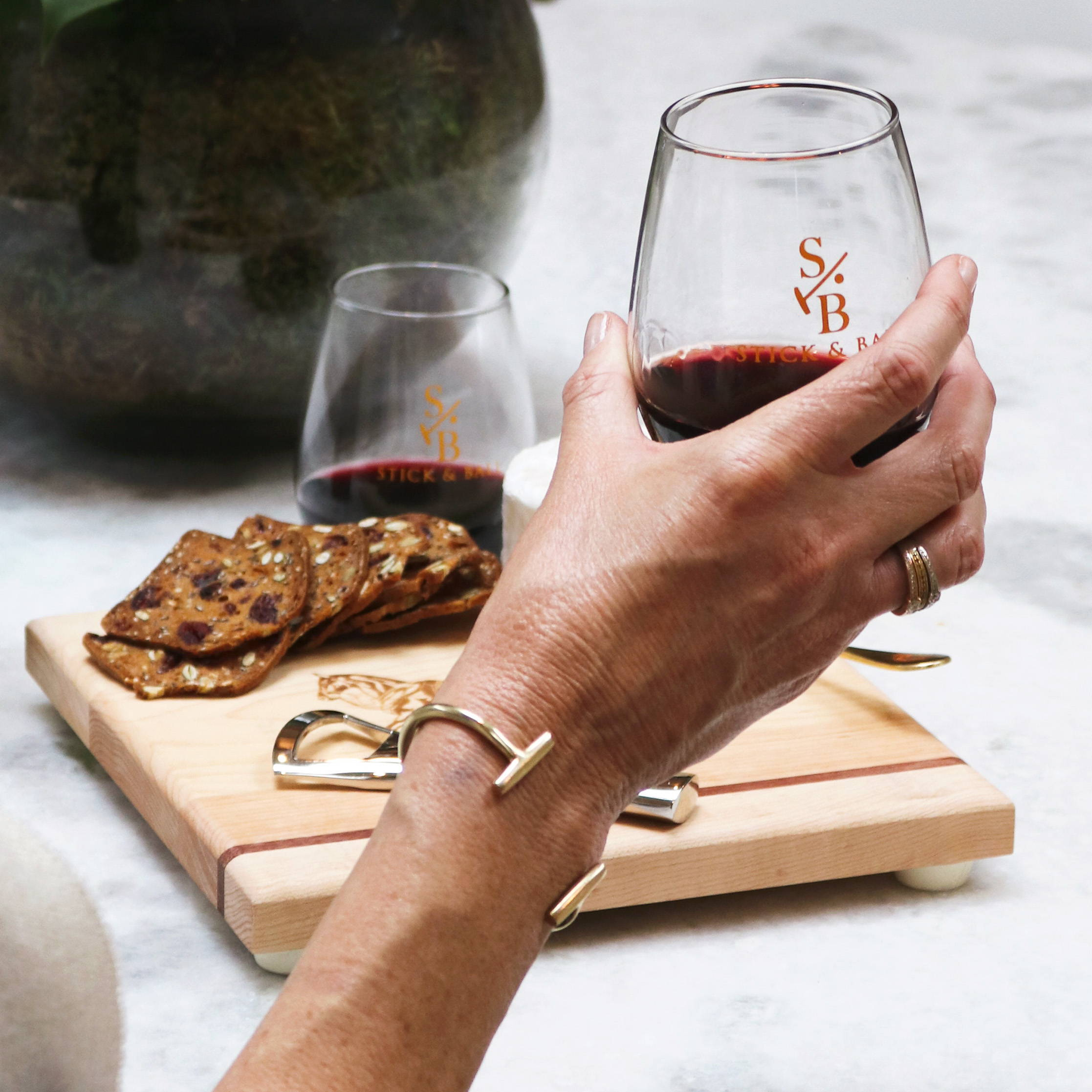 Woman holding a glass of wine in the Stick & Ball Stemless glass with cheese & cracker spread