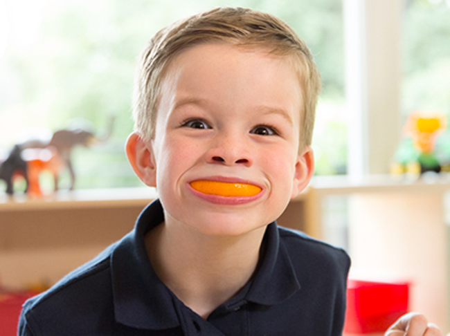 Young Primrose student smiles excitedly with an orange slice in his mouth