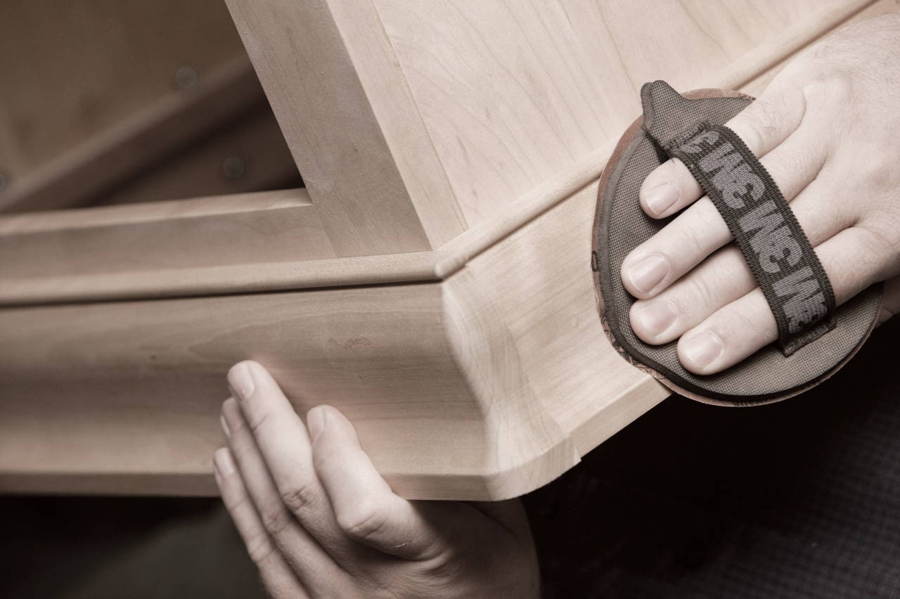 Amish woodworker hand sanding a wood table edge