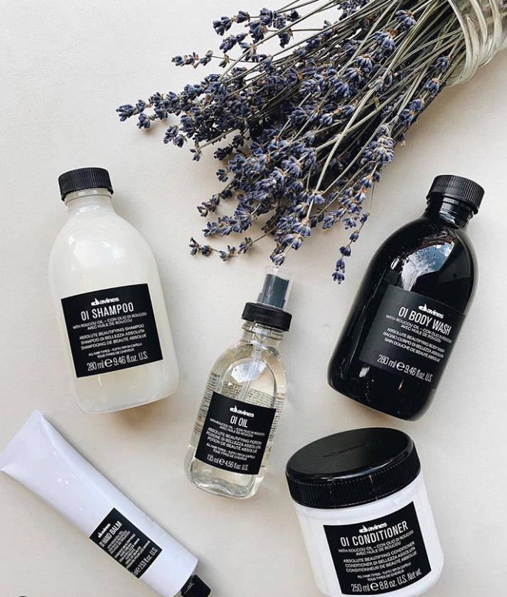 Davines OI Hair products on a cream background with a busshel of lavender