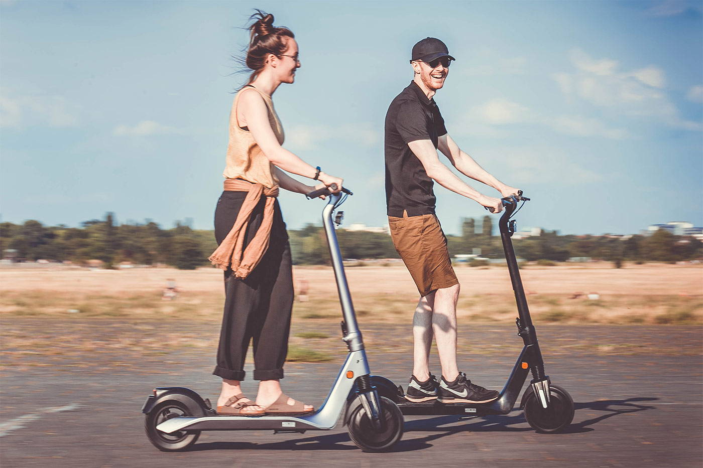 okai-escooter-couple-riding-es500-scooters-smiling