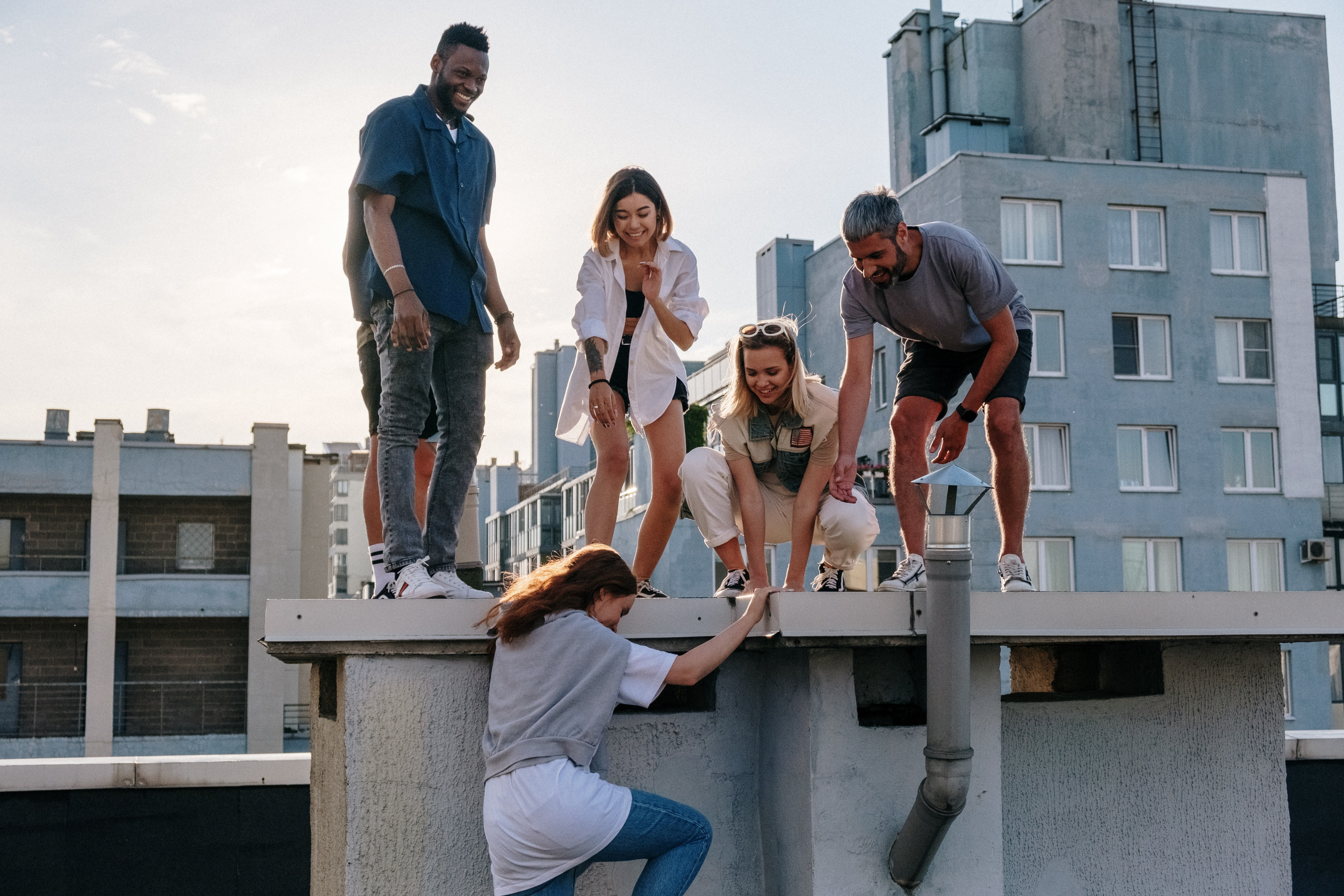 Image of a group of 5 multi ethnic and attractive young men and women. They are all helping one climb to where they are on the roof of a building.