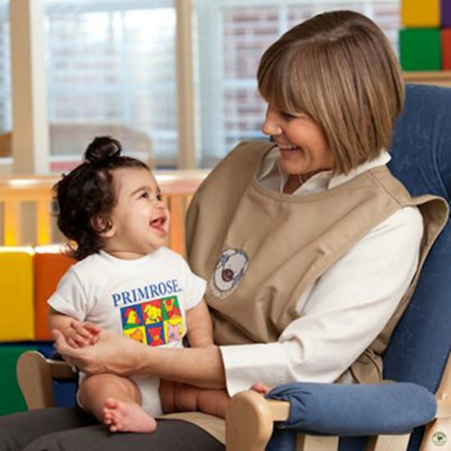 Primrose teacher interacts with an infant sitting on her lap in the infant classroom