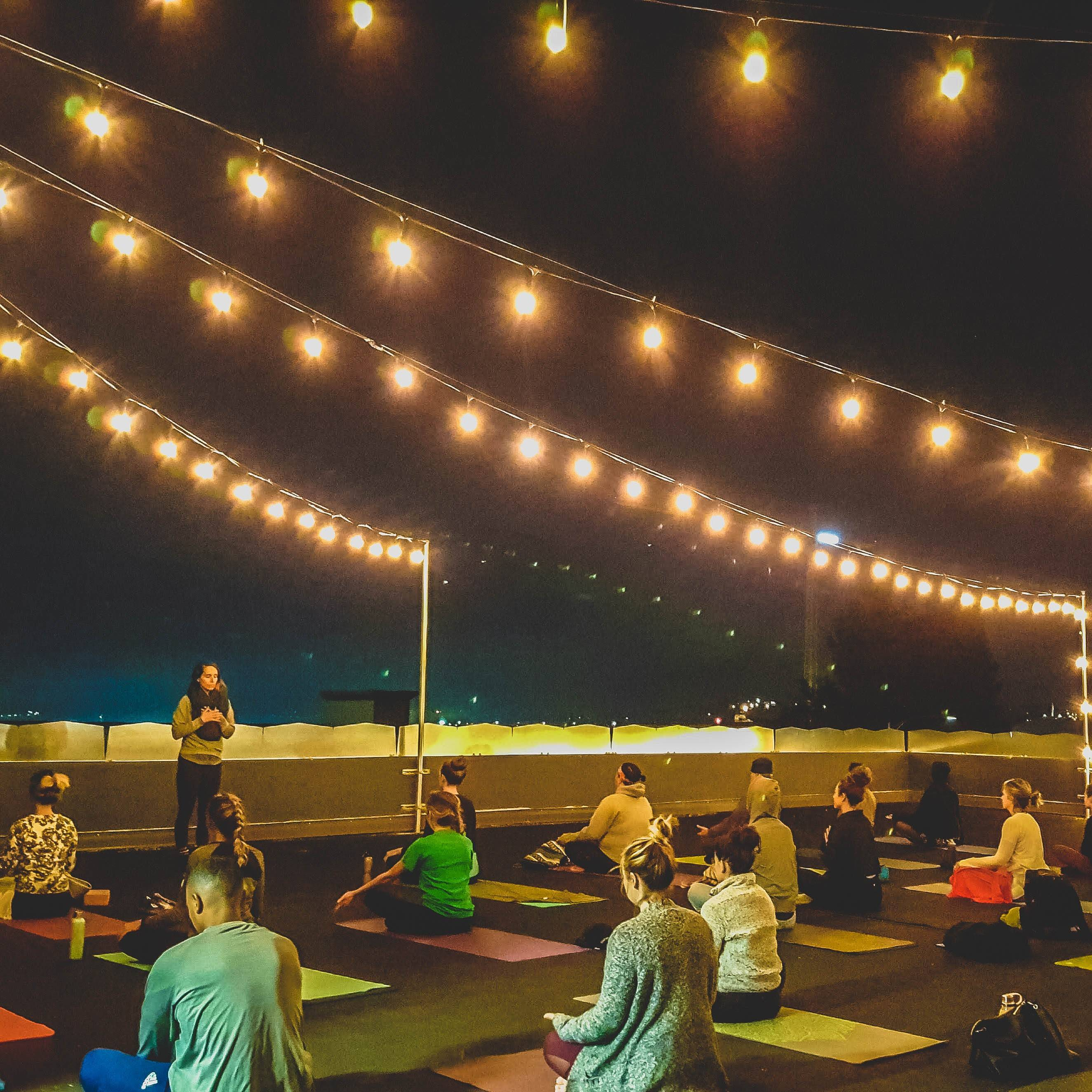 Yoga on a rooftop at night under white string lights.