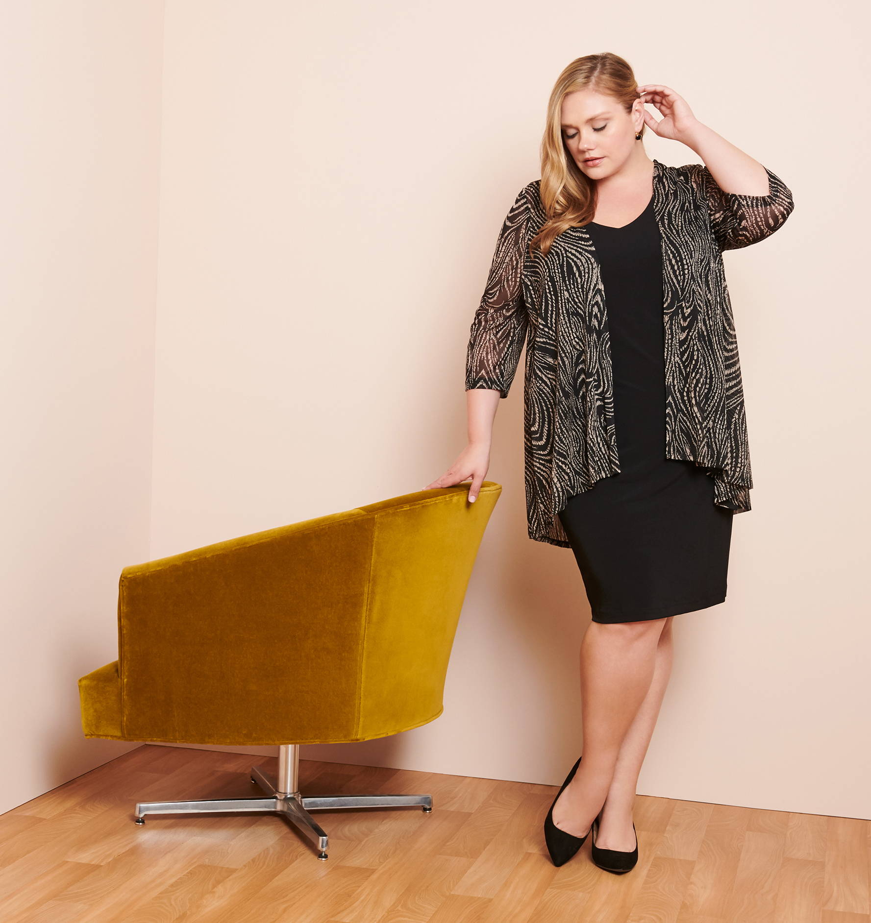 Plus size blonde woman wearing a black sheath dress with zebra mesh jacket overlay leaning on mustard velvet chair