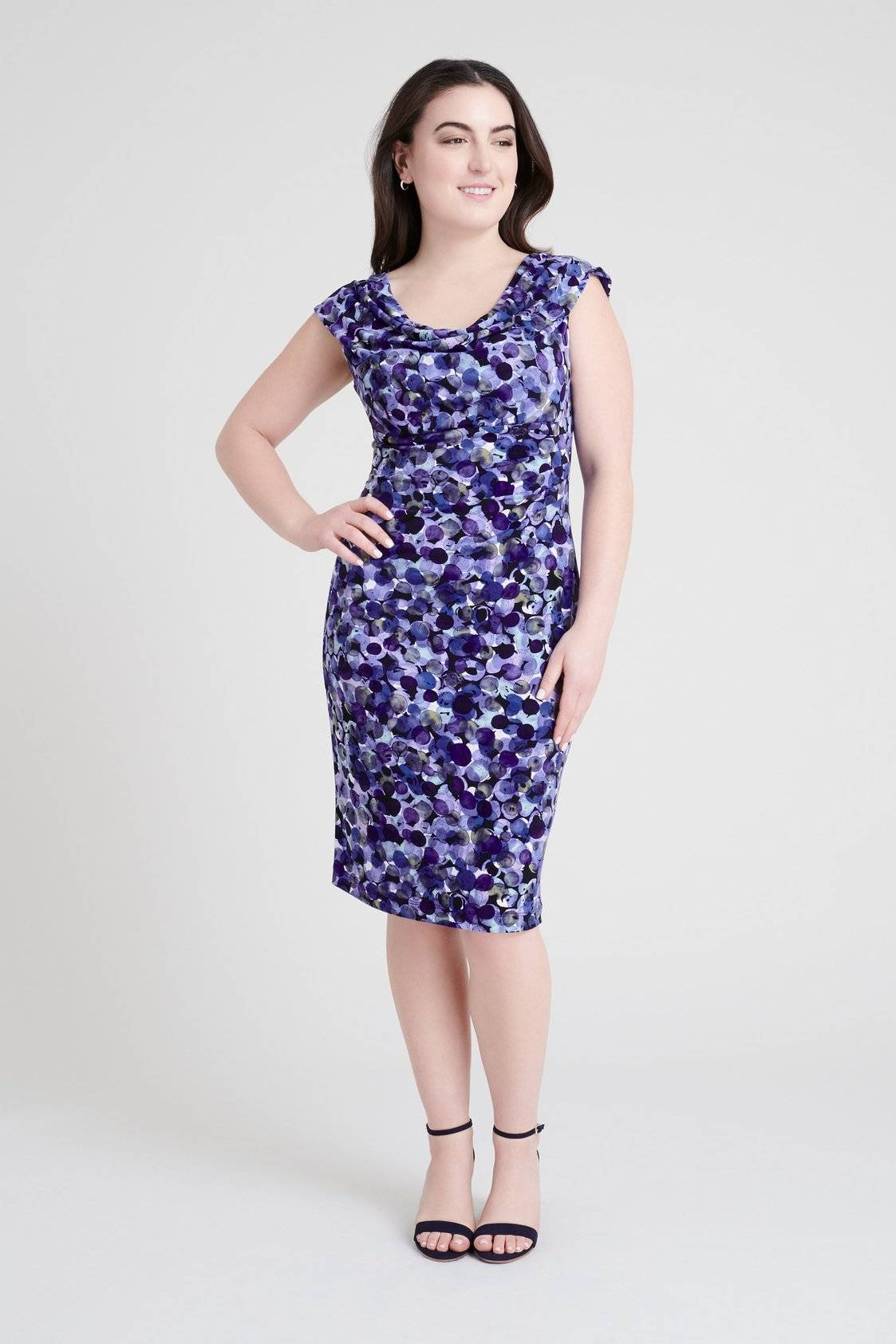 young woman posing in a studio wearing a knee-length vintage style multi-hue purple bubble dot sleeveless dress with cowl neckline from connected apparel