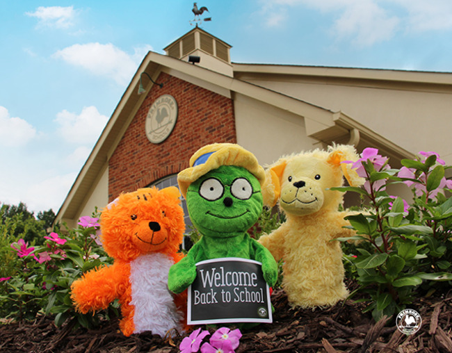 "Primrose puppets Og, Katie and Erwin hold a card saying ""Welcome back to school"" with the Primrose building in the background"