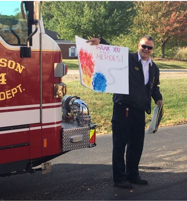 Fire Fighter holding a sign