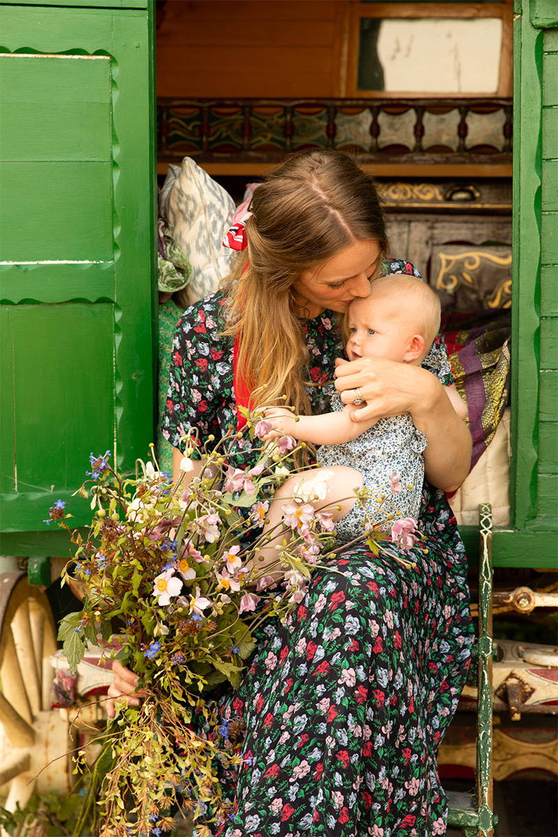 Tess Newall and her baby sit on the sets of her old  gypsy caravan