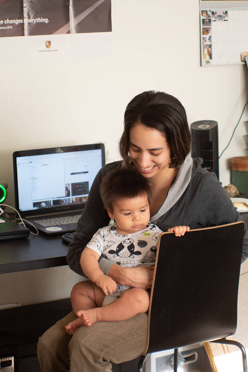 Young women working at laptop with young kid sitting on her lap