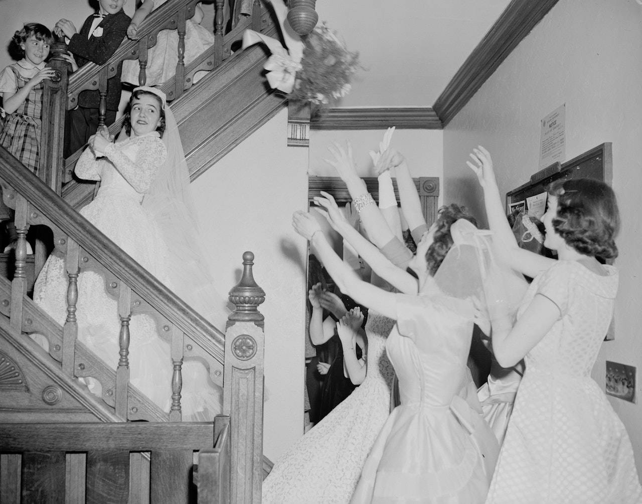 Black and white 50s photo of bride throwing her bouquet | Lily Gardner London