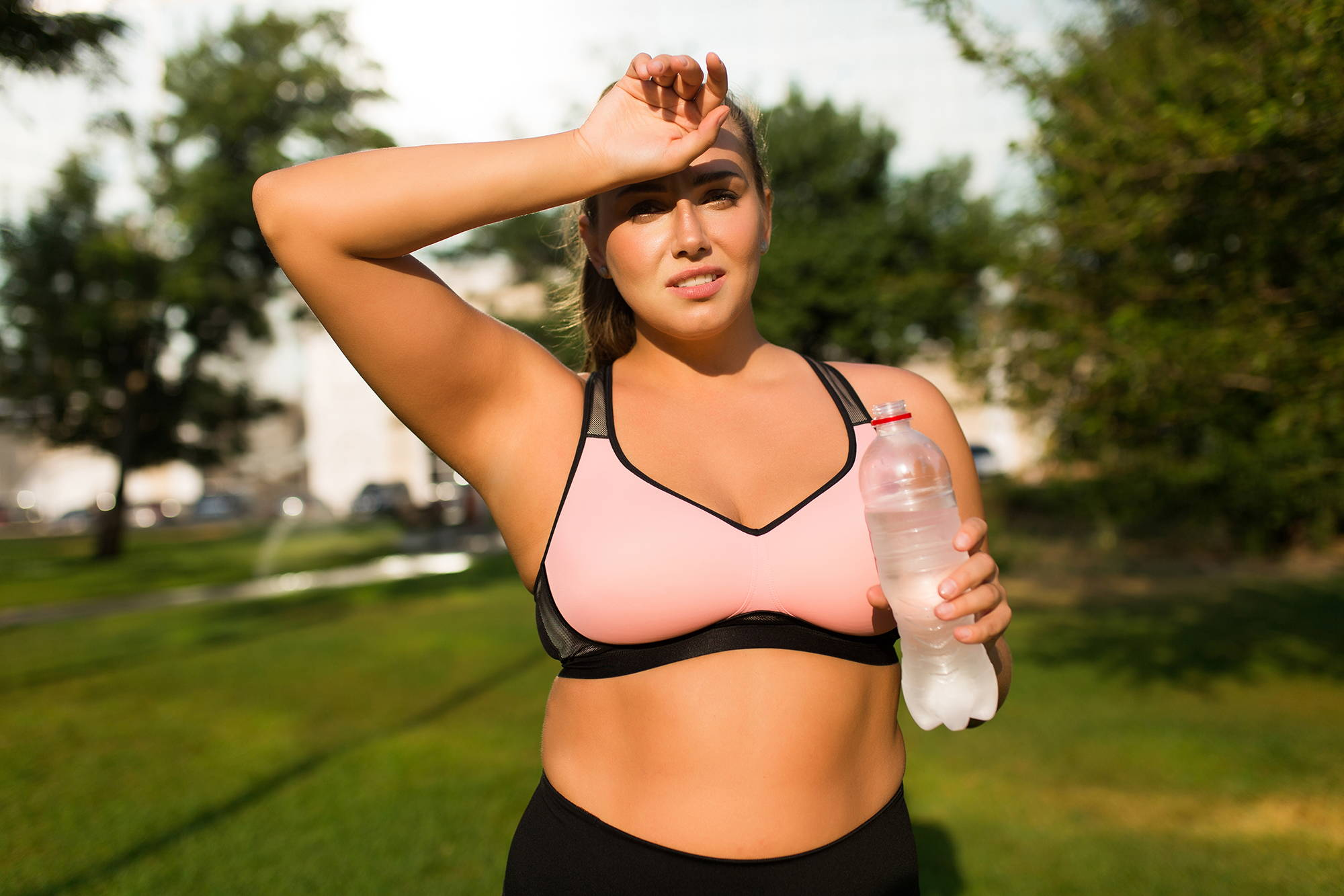 Woman in park exercising with water bottle