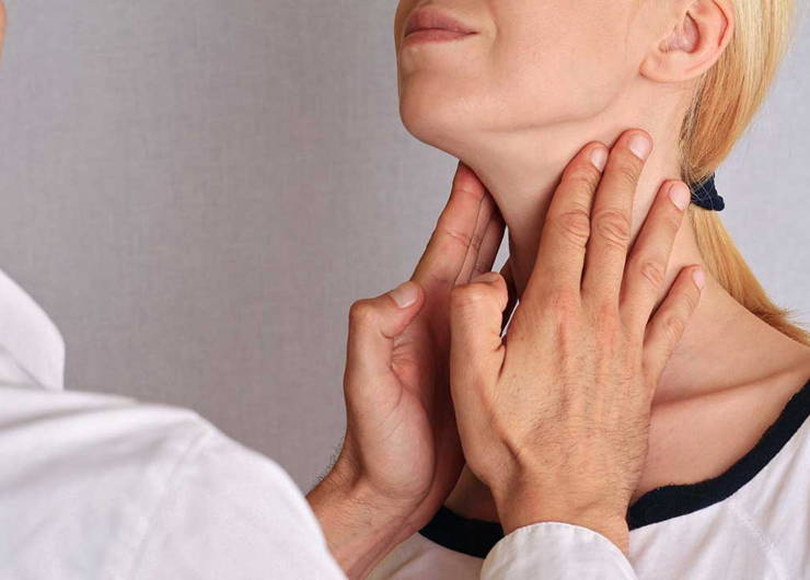 Doctor touching woman's neck.