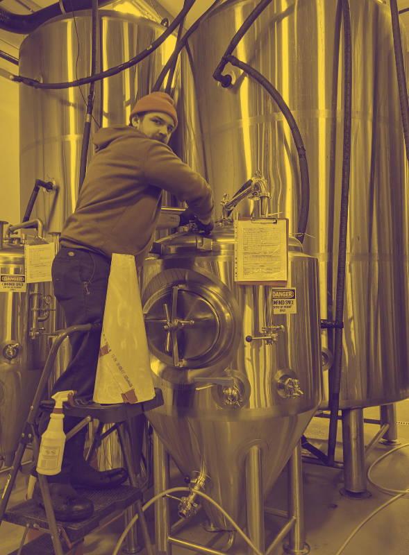 Man unscrewing top lid of beer vault.