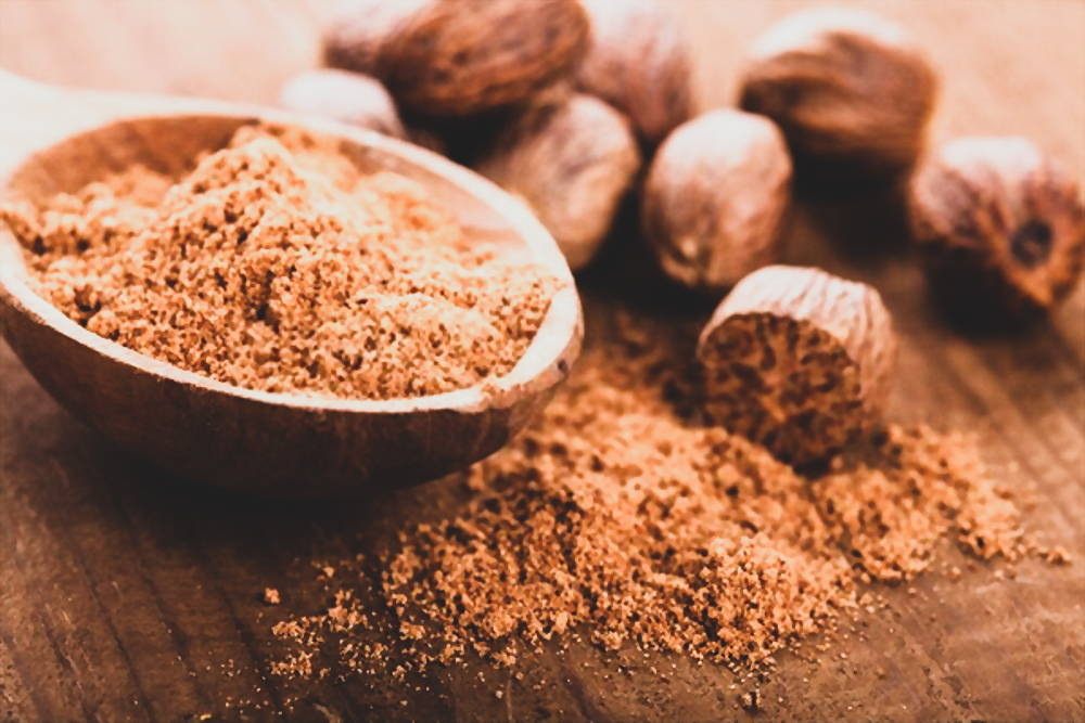 Nutmeg and powder in wooden bowl