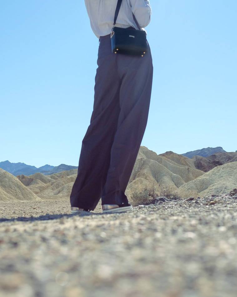 Black ecofriendly vegan leather pouch worned with oversized high-waist pants in the desert