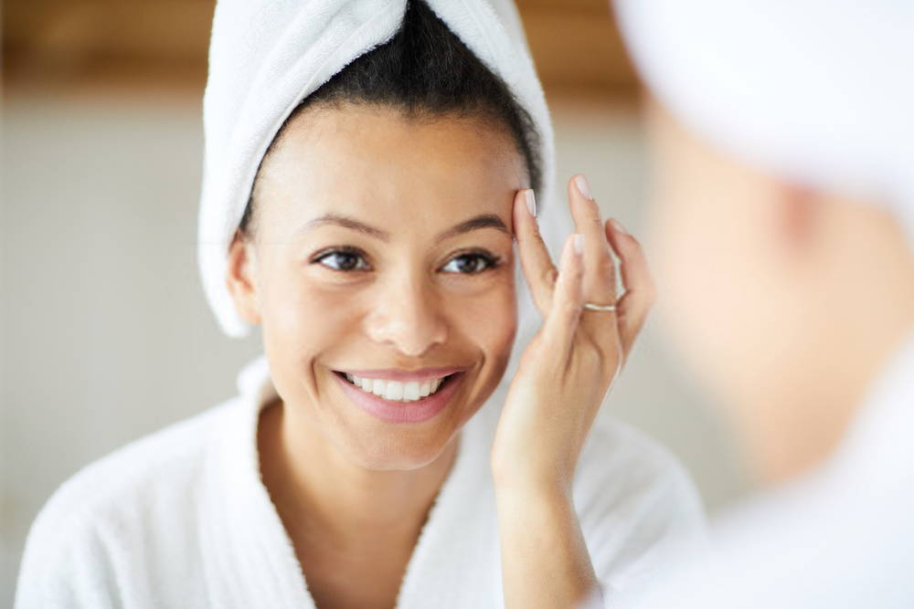 young woman looking in mirror as she applies face cream
