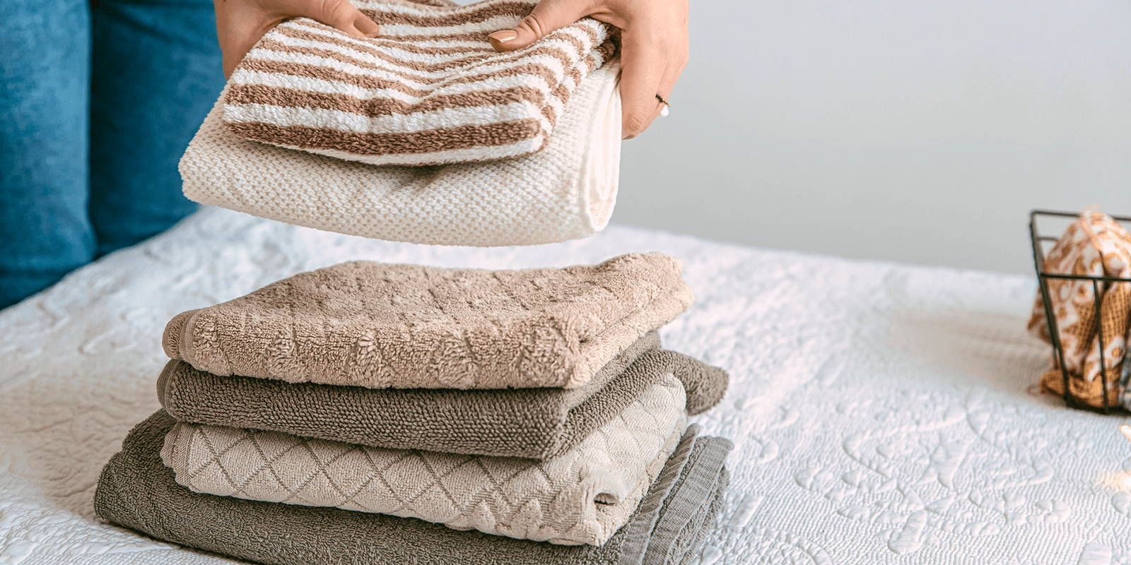 Hands setting folded towels on bed.