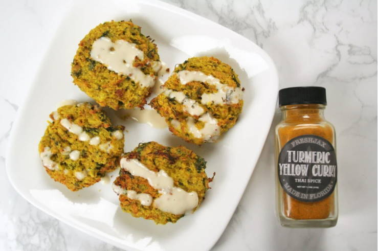 A plate of cauliflower falafel next to a small bottle of FreshJax Organic Turmeric Yellow Curry Thai Spice.