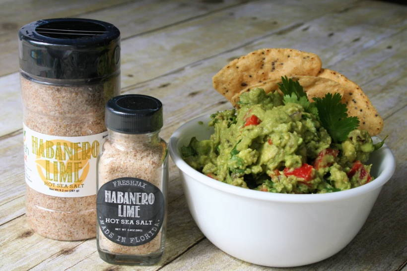 Two bottles of FreshJax Habanero Lime Hot Sea Salt next to a bowl of Spicy habanero lime guacamole.