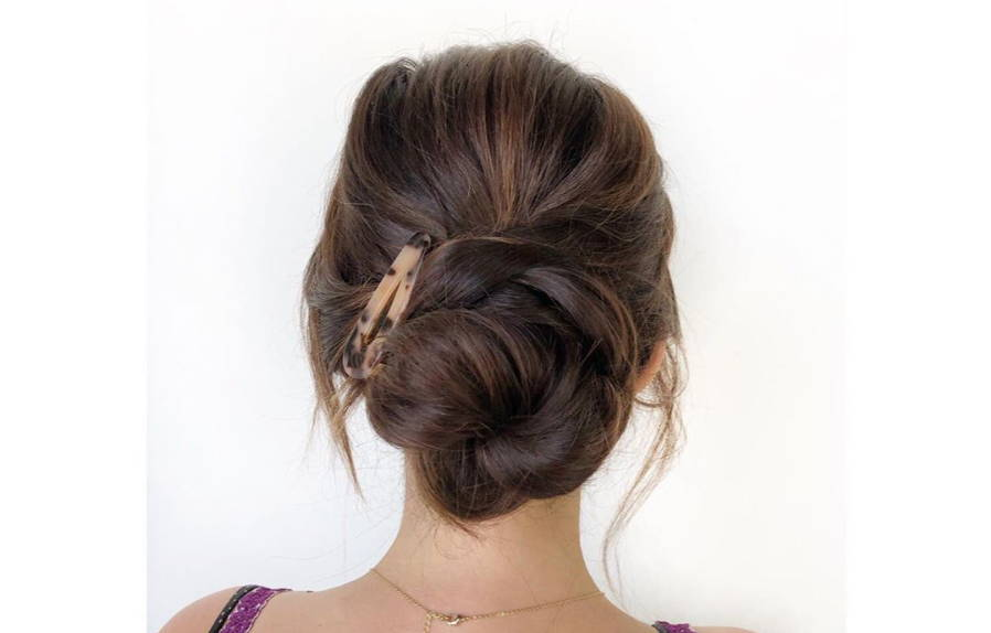 backview of a brunette woman with a bun and a barette in her hair
