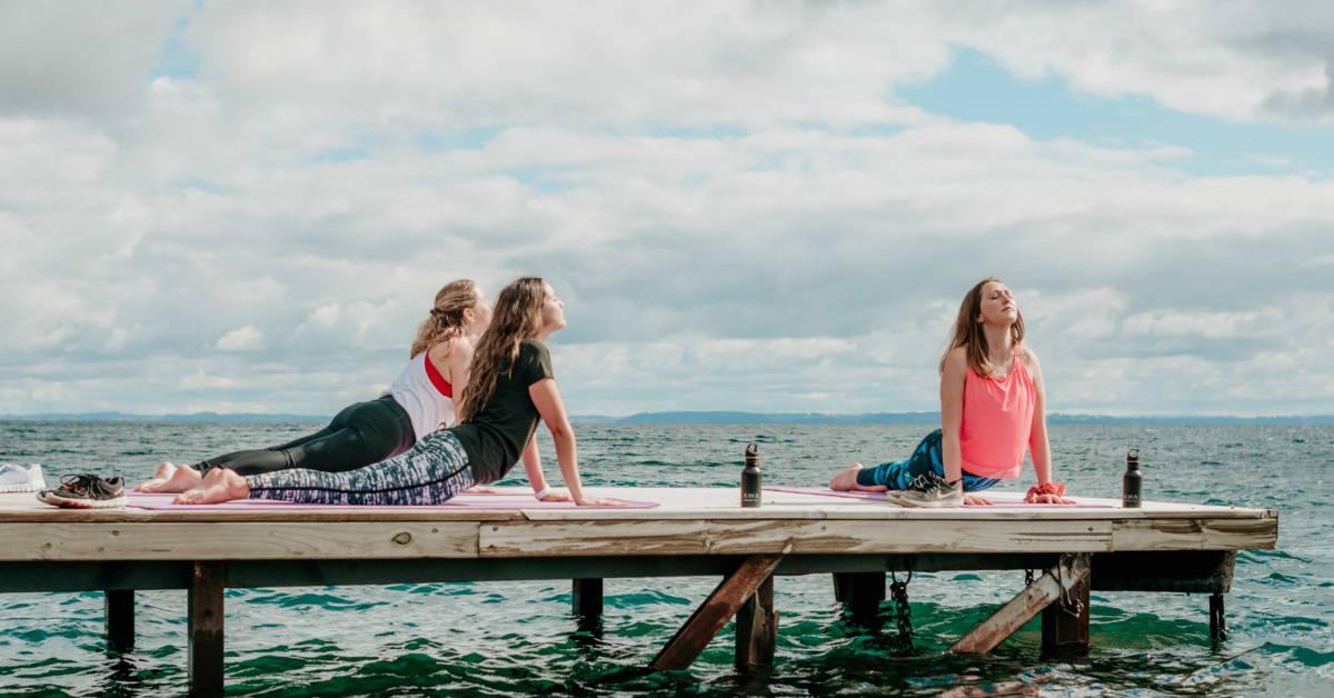 Three women practicing yoga on dock over ocean