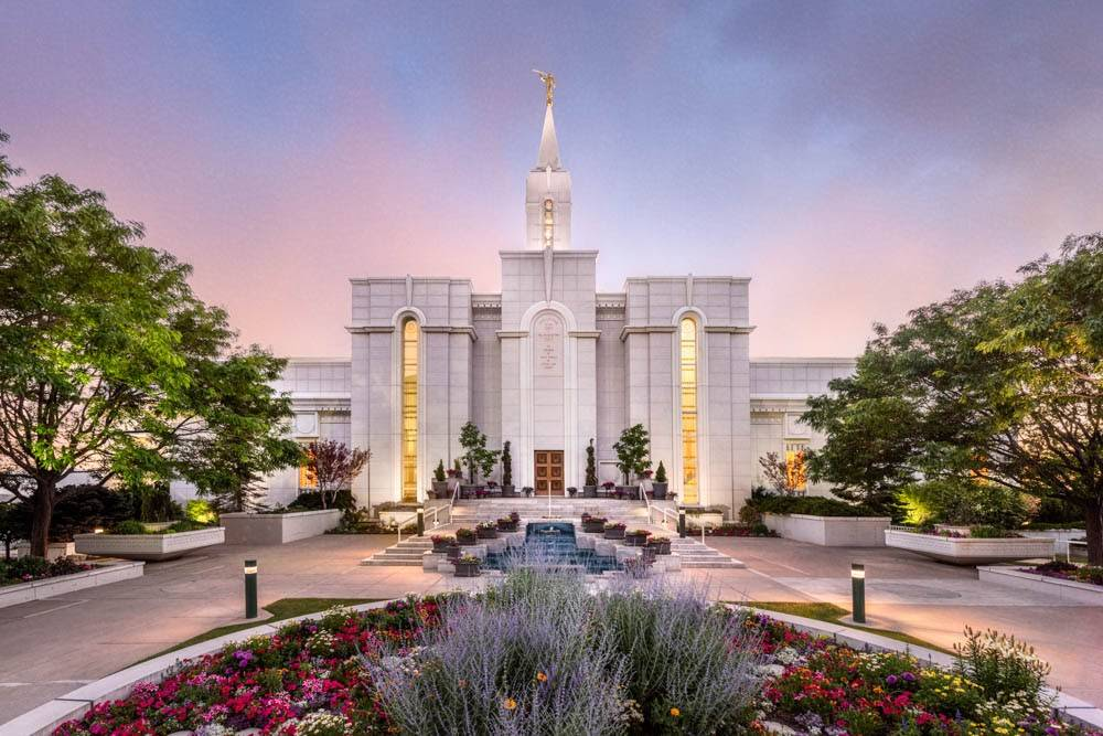 LDS art photo of the Oquirrh Mountain Temple against a pink sky with spring flowers.