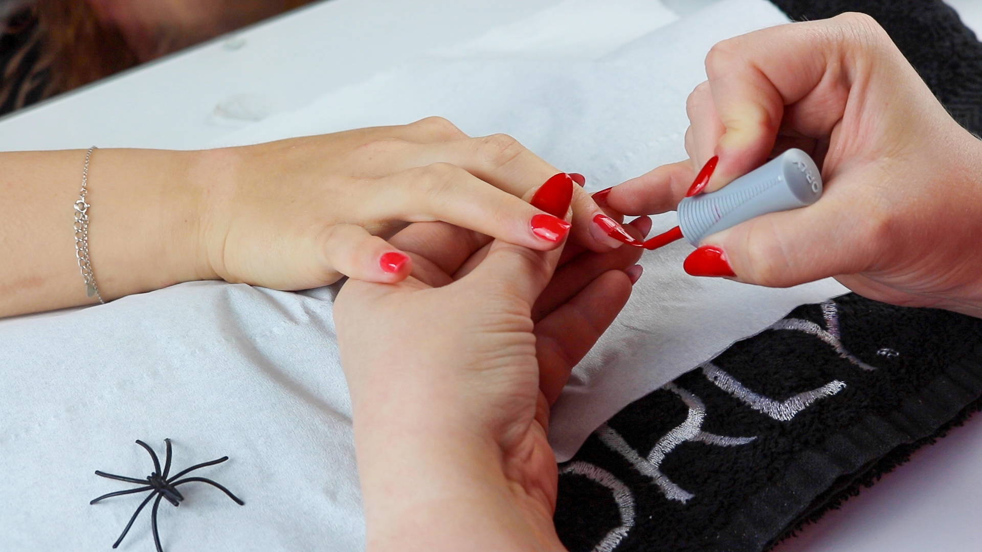 Harley Quinn nails being painted with ORLY Haute Red
